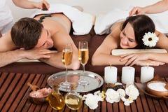 Couple enjoying hot stone massage at spa. Smiling young couple enjoying hot stone massage at beauty spa royalty free stock photo