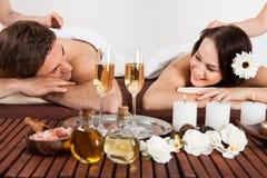 Couple enjoying hot stone massage at spa. Smiling young couple enjoying hot stone massage at beauty spa royalty free stock photos