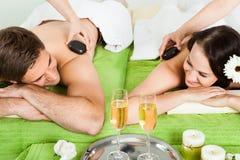 Couple Enjoying Hot Stone Massage At Spa Stock Image