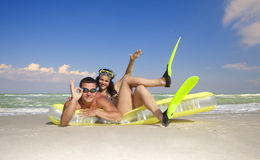 Couple enjoying on an inflatable beach mattress Stock Photos