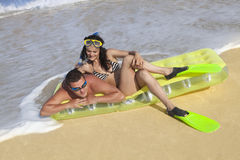 Couple enjoying on an inflatable beach mattress Royalty Free Stock Images