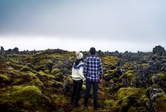 Couple enjoying lava field view in Iceland. Couple enjoying lava field scenery in Iceland travel green person love girl standing icelandic female man sitting stock photo