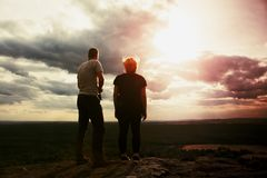 Couple enjoying marvellous moments during sunset . Young pair of hikers on the peak of rock watch over valley to Sun. Royalty Free Stock Photos
