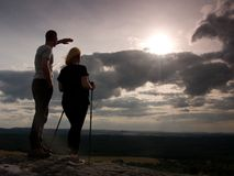 Couple enjoying marvellous moments during sunset . Young pair of hikers on the peak of rock watch  to Sun. Royalty Free Stock Photos