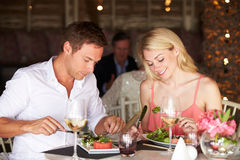 Couple Enjoying Meal In Restaurant Stock Image