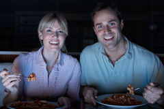 Couple Enjoying Meal Whilst Watching TV Royalty Free Stock Image