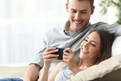 Couple enjoying media content in a smart phone Royalty Free Stock Images