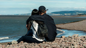 Couple enjoying Minehead. Happy young couple in love relaxing in a  beach of Minehead, UK  enjoying ocean view together sitting in the sand embracing and hugging Royalty Free Stock Photo
