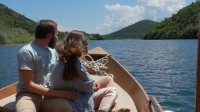 Couple enjoying a motor boat ride on the lake on a sunny day. Slow motion stock video footage