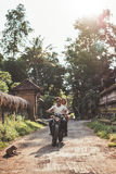 Couple enjoying motorcycle ride through a village road. Royalty Free Stock Photo