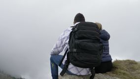 Couple enjoying the mountain excursion sitting on high cliff and admiring the beauty of nature with misty forests and green hills. Young couple enjoying the stock footage