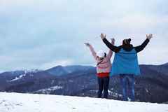 Couple enjoying mountain landscape, space for text. Winter vacation royalty free stock photo