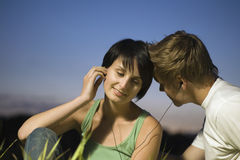 Couple Enjoying Music Through Earphones Royalty Free Stock Images