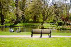 Couple enjoying nature. A couple sitting beside a pond, relaxing. Great for health in nature, relaxation articles Royalty Free Stock Images
