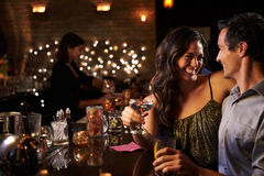 Couple Enjoying Night Out At Cocktail Bar Royalty Free Stock Photography