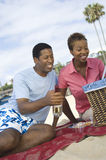 Couple Enjoying Picnic On The Beach Stock Photo
