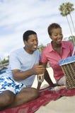 Couple Enjoying Picnic On The Beach. Happy African American couple enjoying picnic on the beach Stock Photo