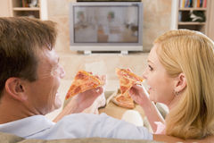 Couple Enjoying Pizza In Front Of TV Stock Images