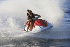 Couple Enjoying PWC Ride. Young couple enjoying the ride of personal watercraft on lake Stock Photography