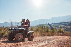 Couple enjoying a quad bike ride in countryside Royalty Free Stock Photo