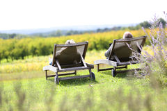 Couple enjoying quiet moment in long chairs Stock Photography