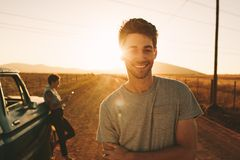 Couple enjoying on a road trip. Close up of smiling men standing on a mud track with his partner in the background. Couple enjoying their road trip in country stock images