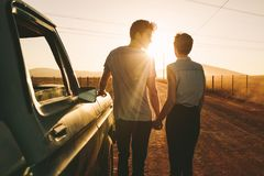 Couple enjoying on a road trip. Romantic couple standing holding hands beside their pickup truck during a road trip in country side. Rear view of couple holding stock image