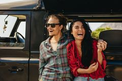 Couple enjoying on a roadtrip. Cheerful young couple taking a break on roadtrip. Young men and women standing by their car and laughing stock image
