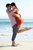 Couple Enjoying Romantic Beach Holiday. Cuddling Stock Photo