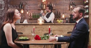 Couple enjoying a romantic date with candles in a restaurant stock footage