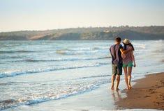 Couple enjoying a romantic evening on the beach at sunset Stock Image