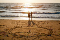 Couple enjoying a romantic evening on the beach at sunset Royalty Free Stock Image