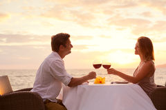 Couple enjoying romantic sunnset dinner. Couple sharing romantic sunset dinner on the beach Stock Photos