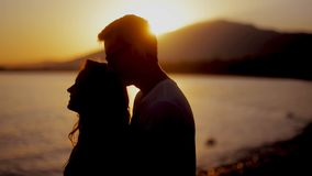 Couple enjoying a romantic sunset evening together on the beach. Couple silhouette at the beach. Sunset light. Smile. stock video