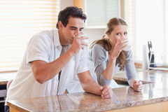 Couple enjoying some milk in the kitchen Stock Images