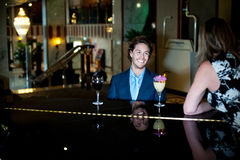 Couple enjoying soothing music as guy plans piano. For her lady Royalty Free Stock Photo