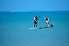 Couple enjoying stand up paddle board on blue sea background 1 stock image