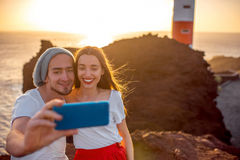 Couple enjoying summer vacation near the lighthouse. Romantic couple dressed in white and red taking selfie photo with rocks, lighthouse and oecan on the Royalty Free Stock Photography