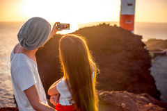 Couple enjoying summer vacation near the lighthouse. Romantic couple dressed in white and red taking selfie photo with rocks, lighthouse and oecan on the Royalty Free Stock Photos