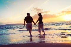 Couple Enjoying Sunset at the Beach. Senior Couple Enjoying Tropical Sunset at the Beach royalty free stock photo