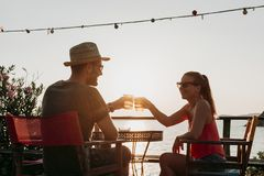 Couple enjoying sunset in a beach bar drinking beer. Young couple enjoying sunset in a beach bar drinking beer royalty free stock images