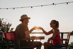 Couple enjoying sunset in a beach bar drinking beer. Young couple enjoying sunset in a beach bar drinking beer royalty free stock photo