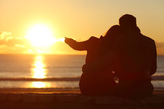 Couple enjoying sunset on the beach in winter Stock Images