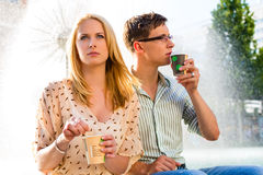 Couple enjoying take away coffee in a break Royalty Free Stock Image