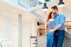 Couple enjoying their new luxurious home. And hugging in living room stock images