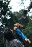 Couple enjoying themselves in rain at forest. Man and women spending free time in forest during rain royalty free stock photography