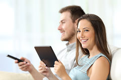 Couple enjoying tv and looking you Royalty Free Stock Photo