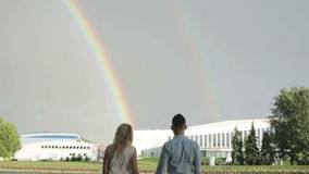 A couple enjoying two rainbows in the sky. stock video footage
