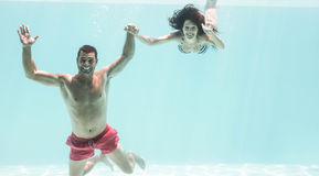 Couple enjoying underwater in swimming pool Stock Photos