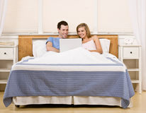 Couple enjoying using laptop in bed Royalty Free Stock Images